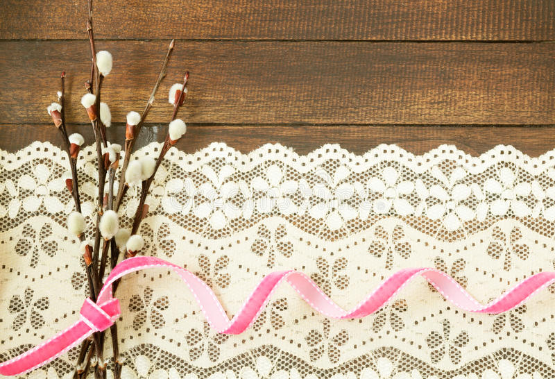 Branches of willow with pink ribbon. On wooden background royalty free stock photography