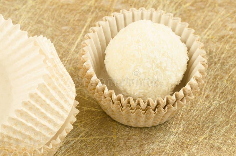 Branco, redondo, o chocolate do coco sua e o empacotamento de papel no fundo dourado imagem de stock royalty free