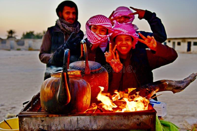 Brand branden op hout met hete vlammen en de Arabische jongens zijn zo gelukkig genietend van het leven stock foto's