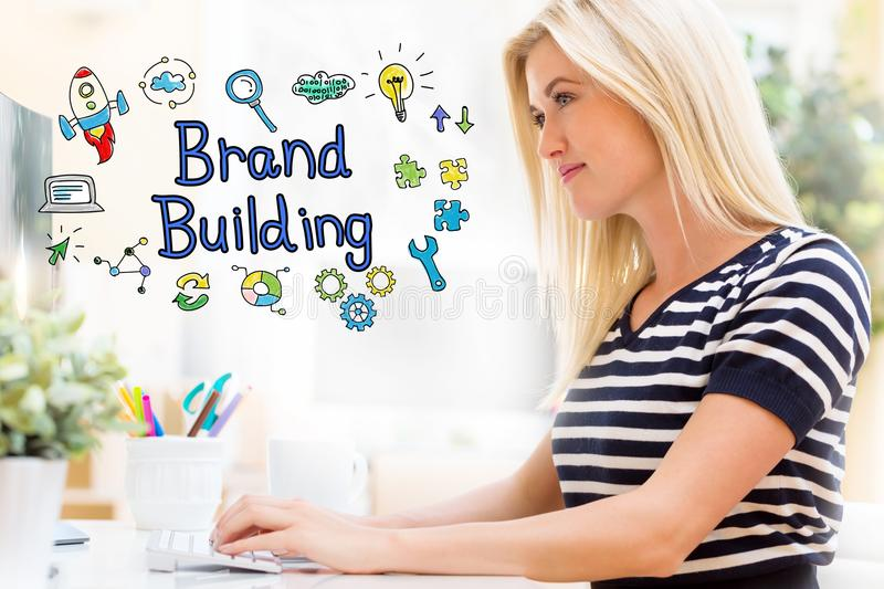 Brand Building with happy young woman in front of the computer royalty free stock photography