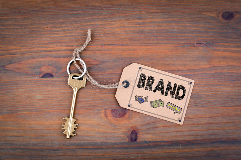 Brand concept. Brass key with a price tag on a wooden table royalty free stock images