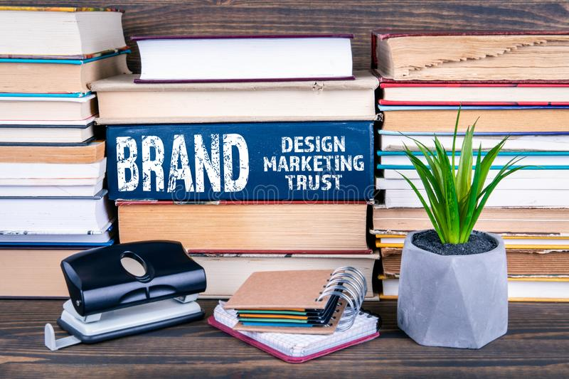 Brand concept. Design, marketing and trust. Books stacked on a wooden table royalty free stock photo