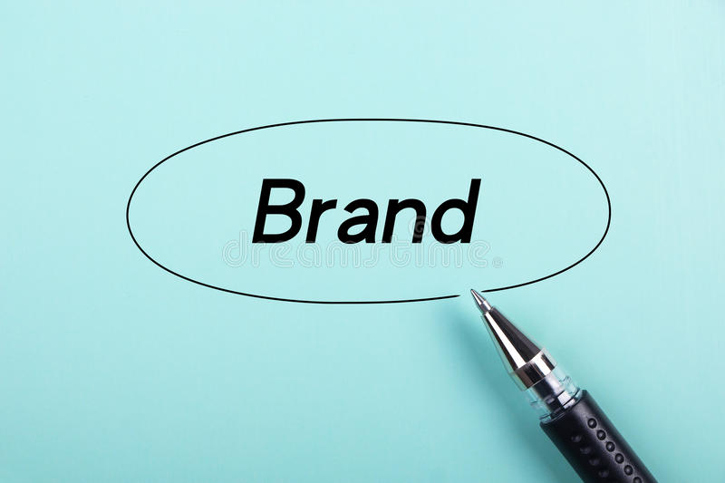 Brand concept. Brand text is on blue paper with black ball-point pen aside royalty free stock photography