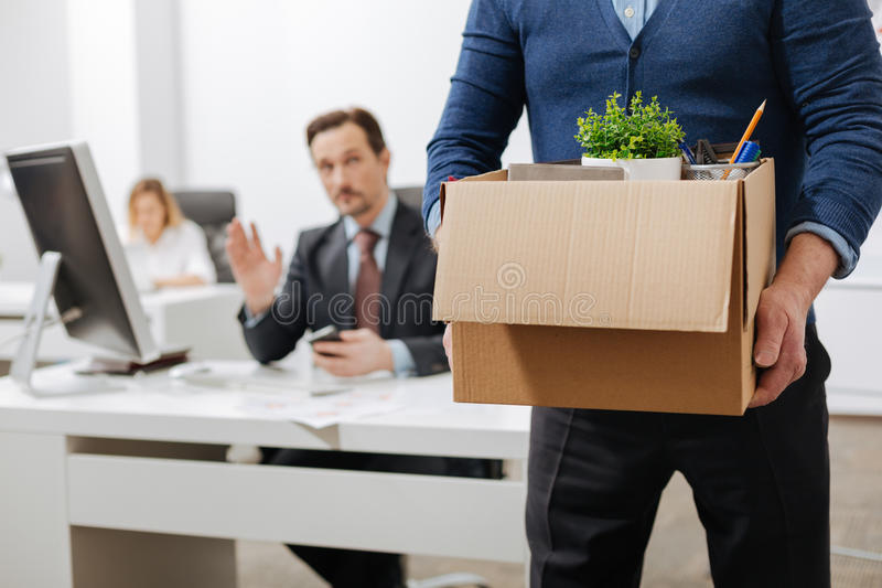 In brand gestoken hogere werknemer die het bureau met de doos verlaten royalty-vrije stock fotografie