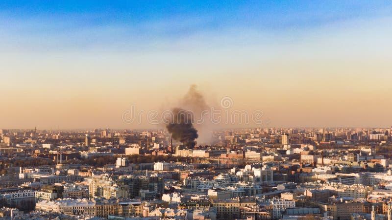 Brand i staden, en kolonn av svart rök stiger ovanför horisonten, flyg- sikt royaltyfria foton