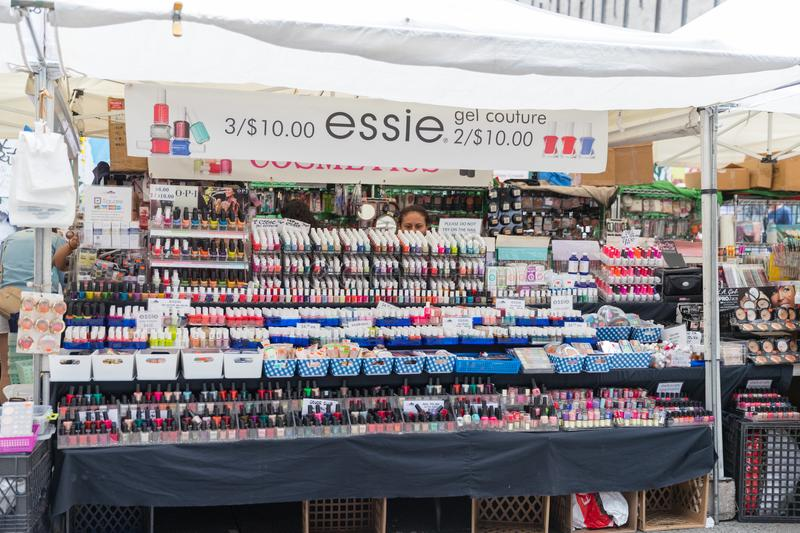 Brand name boutiques and cosmetics booths sell their goods in the New York city street. royalty free stock photos