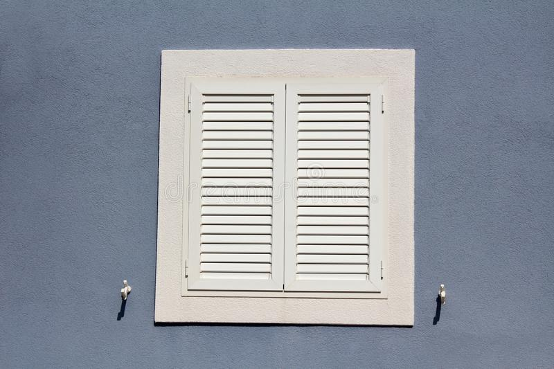 Brand new closed window blinds with metal hinges and holders mounted on house wall with new facade and white frame. On warm sunny day royalty free stock photography