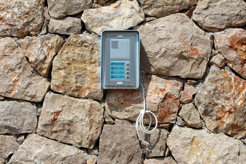 Brand new door entry intercom system mounted on traditional stone wall with hanging electrical wires waiting to be connected stock photos