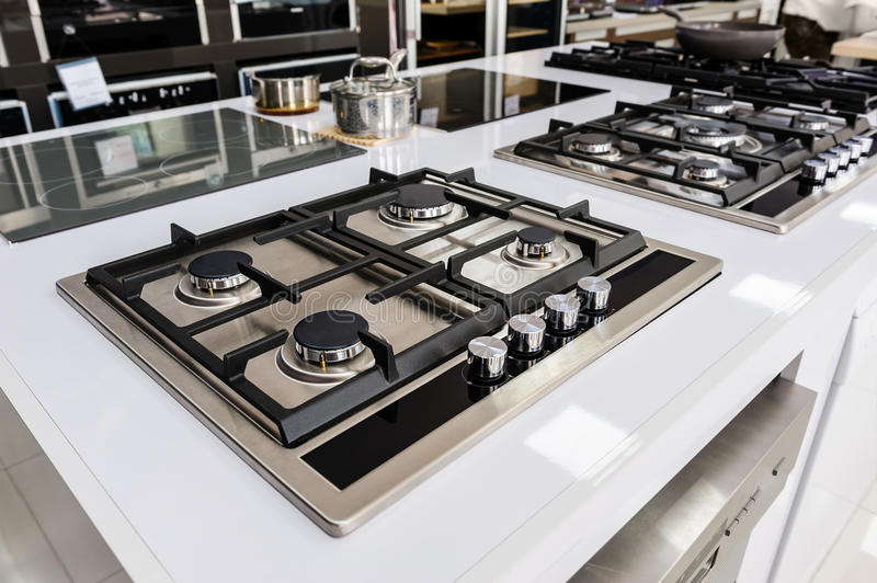 Brand new gas stoves. Rows of gas stoves with stainless tray selling in appliance retail store stock images