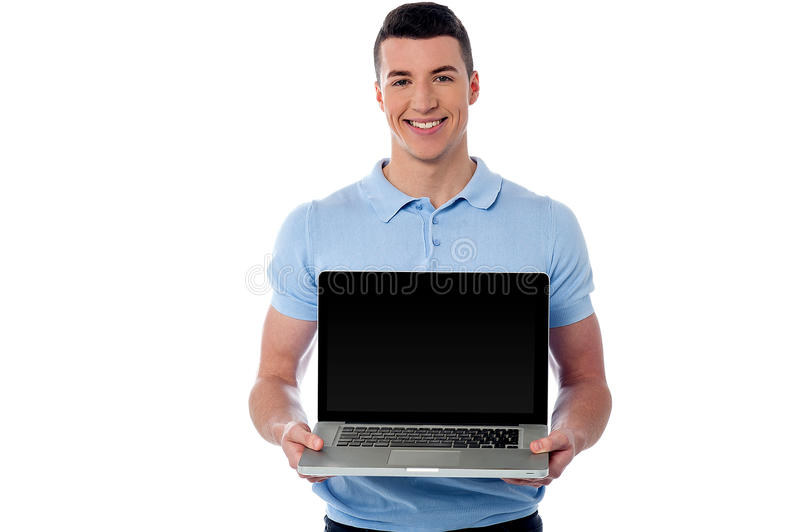 The brand new laptop is out for sale. Handsome young man showing his new laptop royalty free stock photos