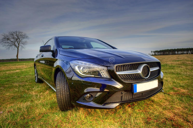 Brand new Mercedes Benz CLA coupe, sideview. Brand new Mercedes Benz CLA coupe in rural scene. Image taken as a wide angle view from the side as a hdr image with royalty free stock photos