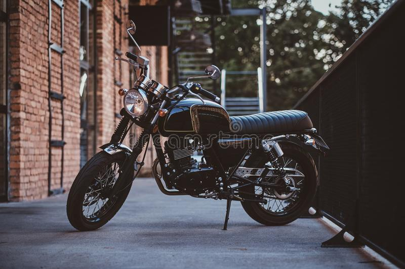 Beautiful retro vintage motorbike near brick wall. Brand new, shiny black retro chopper is parked next to brick building stock photography