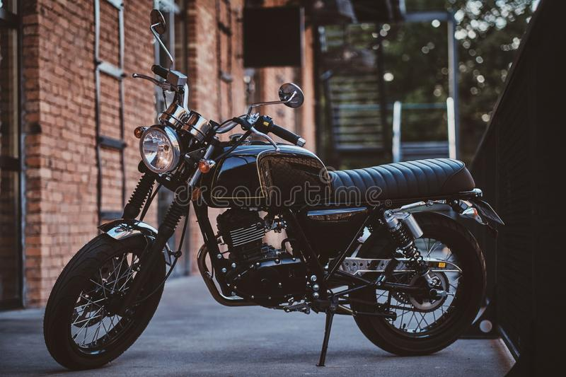 Beautiful retro vintage motorbike near brick wall. Brand new, shiny black retro chopper is parked next to brick building stock images