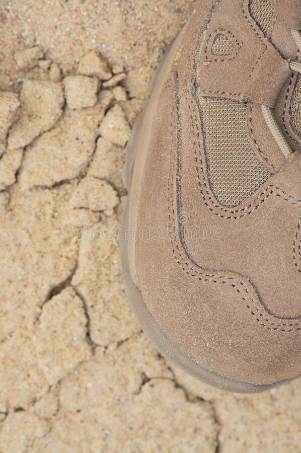 Brand new suede and nylon beige tan camo military tactical desert combat boot, arid dried soil and sand, vertical background stock photo