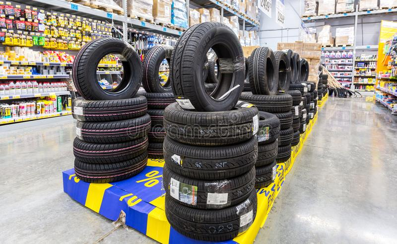Brand new tires stacked up for sale in the chain hypermarket. Samara, Russia - March 24, 2018: Brand new tires stacked up for sale in the chain hypermarket stock images