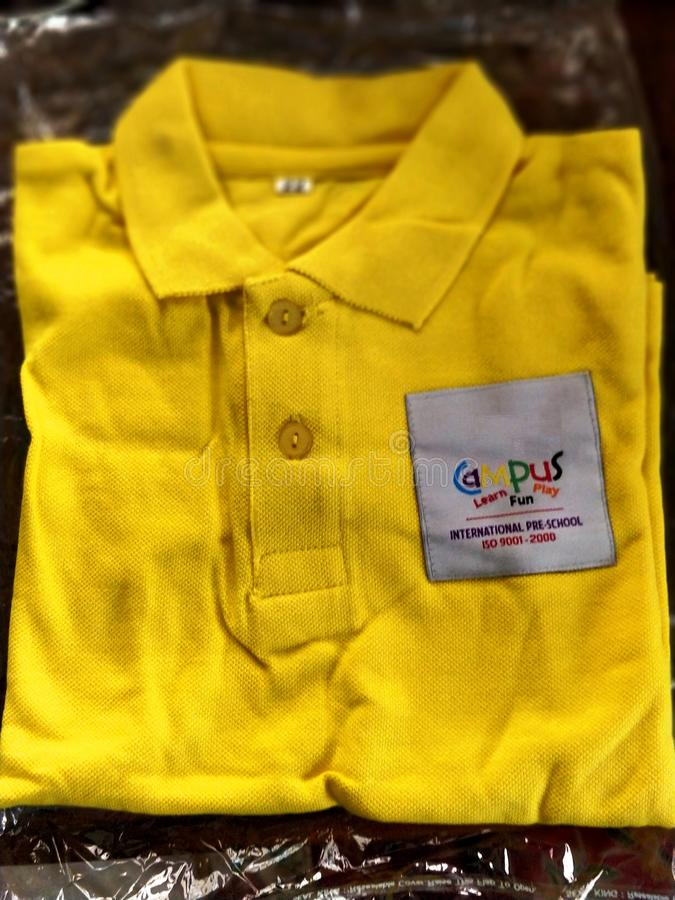 Chennai,TamilNadu/India-0702018: A brand new yellow colored school uniform with school badge royalty free stock photos
