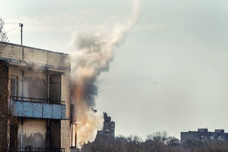 Brand op hoogste vloer van oud flatgebouw Rookwolken het krullen van balkon versleten eclectische bedrading op oud huis en plotse stock foto