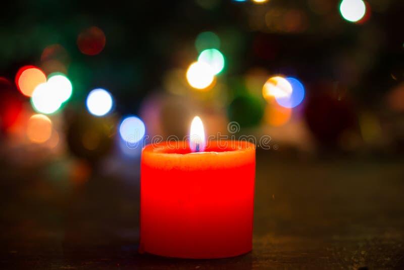 Brand van eenzame rode kaars op Kerstmisachtergrond stock fotografie