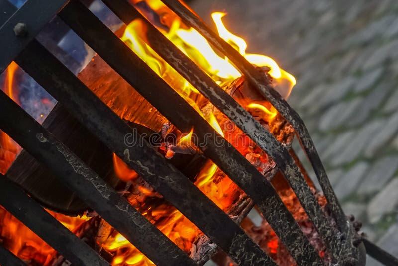 Brand van logboeken van beuk en eiken die hout in een brandmand op een plaats met grijze straatstenen in de winter wordt behandel royalty-vrije stock foto's