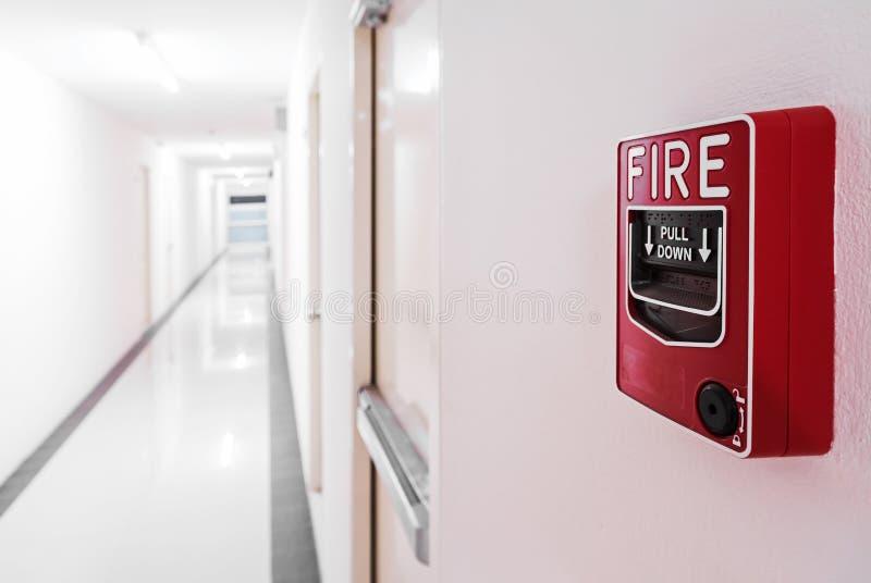 Brandalarm dichtbij de deur van de deurnooduitgang stock fotografie