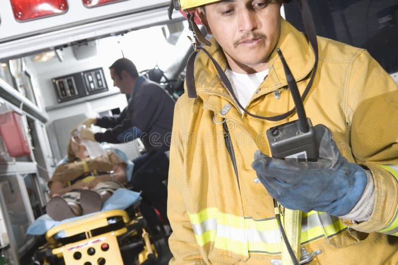 Brandarbetare som rymmer den Walkie talkien med tålmodign och EMT-doktor In Ambulance arkivbild