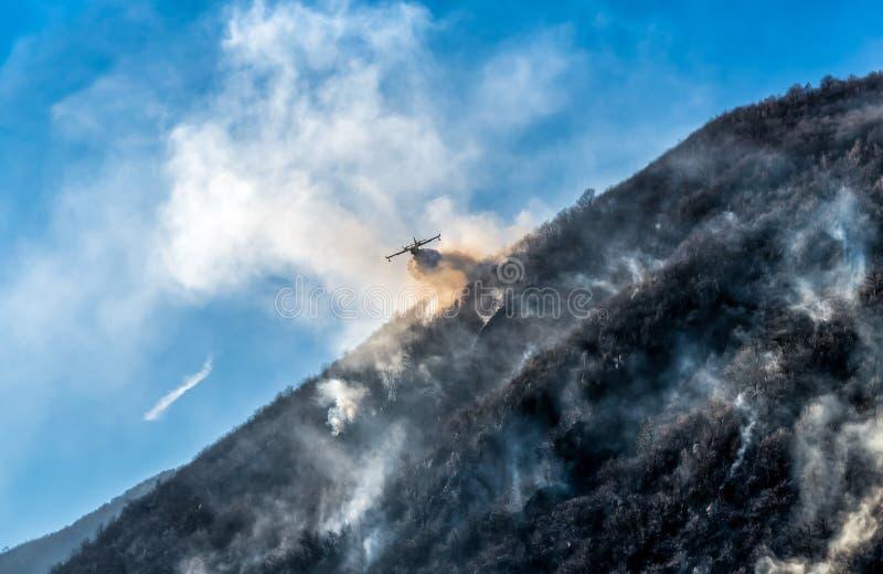 Brandbekämpningflygplan som tappar vattnet för att slåss en brand på berget arkivfoto