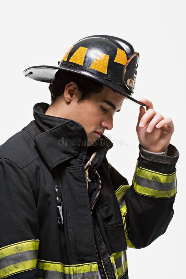 Brandbestrijder die zijn hoed tippen stock foto