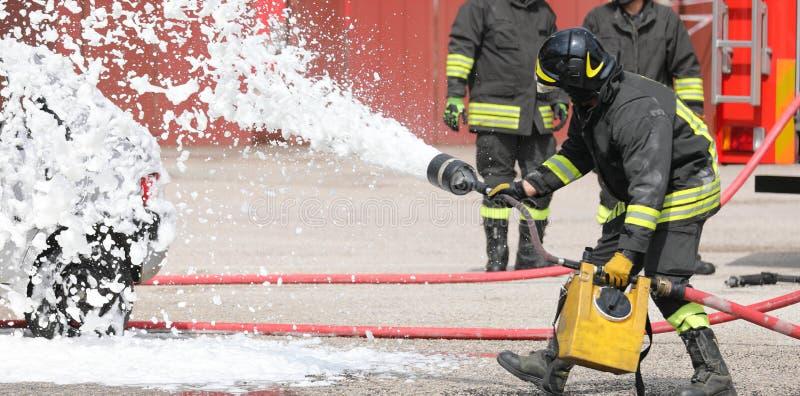 brandbestrijder met schuim de auto na verkeersongeval stock foto