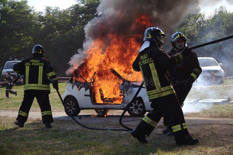Brandbestrijders die auto op brand doven royalty-vrije stock fotografie