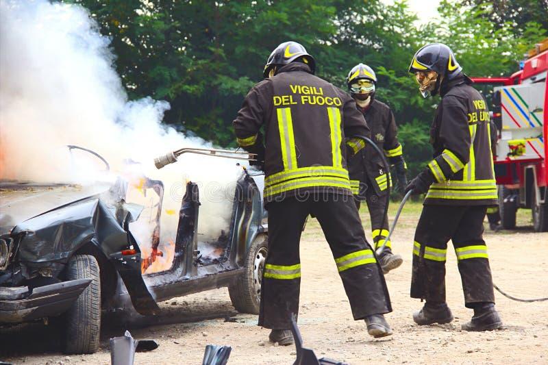 Brandbestrijders die auto op brand doven stock foto's