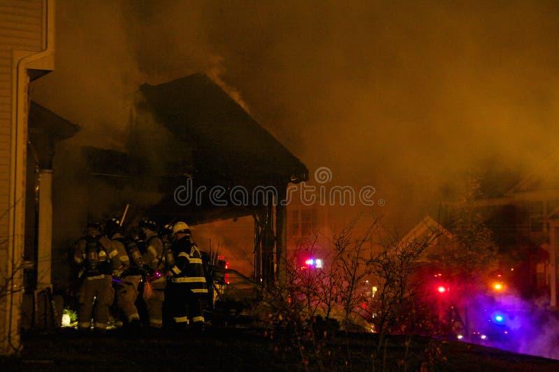 Brandbestrijders die in een Brandend Huis breken royalty-vrije stock afbeelding