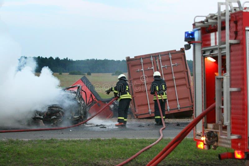 Brandbestrijders die een brandende auto doven royalty-vrije stock afbeelding