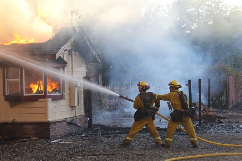 Brandbestrijders die een structuurbrand vechten royalty-vrije stock fotografie