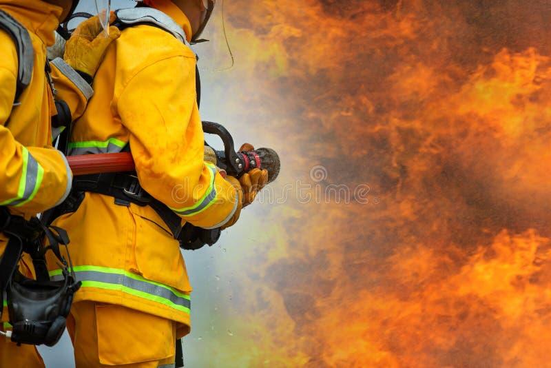 Brandbestrijders die hoge drukwater bespuiten aan brand met exemplaar ruimte, Groot vuur in opleiding, Brandbestrijder die een br royalty-vrije stock fotografie