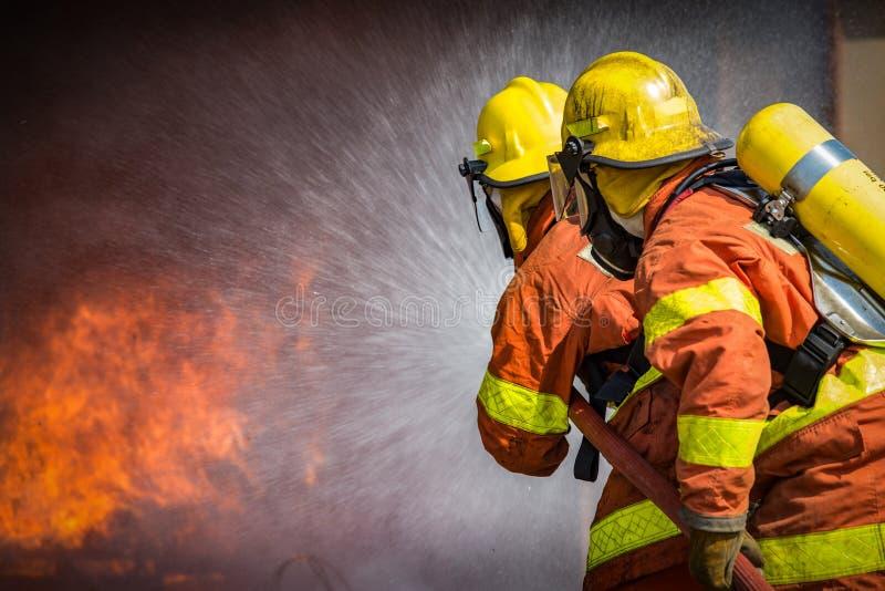 2 brandbestrijders die hoge drukwater bespuiten aan brand met exemplaar s stock afbeelding