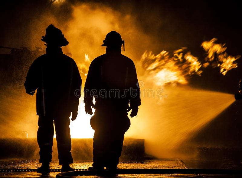 Brandbestrijders die onderaan een brand met water hosing stock afbeelding
