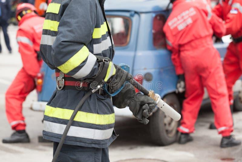 Brandbestrijders in een reddingsverrichting na verkeerongeval stock foto
