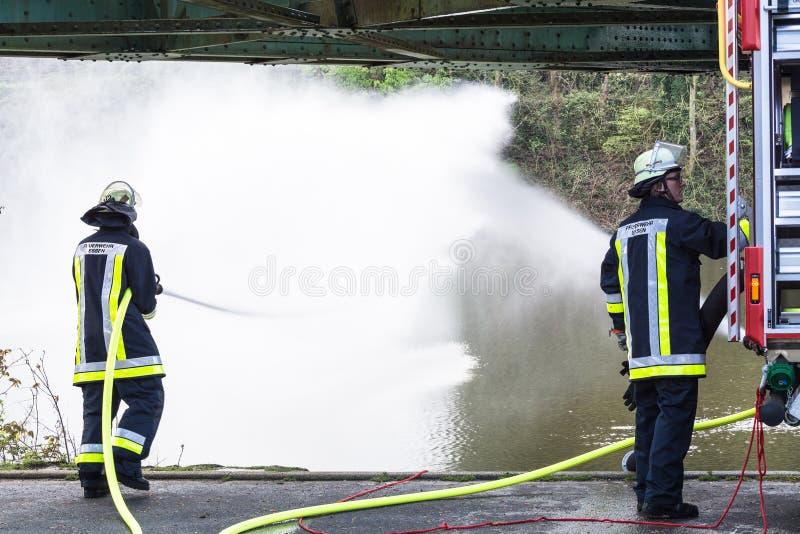 Brandbestrijders in Eenvormig tijdens opleiding stock afbeelding