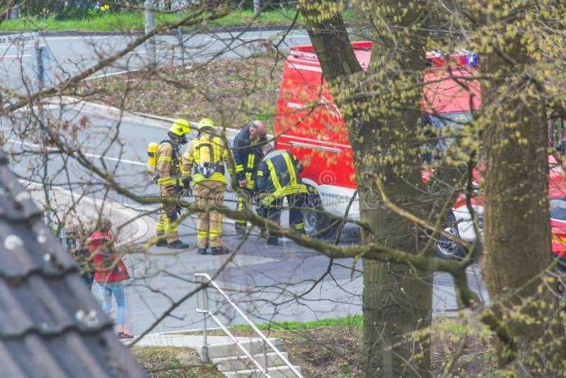 Brandbestrijders met ademhalingsmaskers vóór brandvrachtwagen royalty-vrije stock afbeelding
