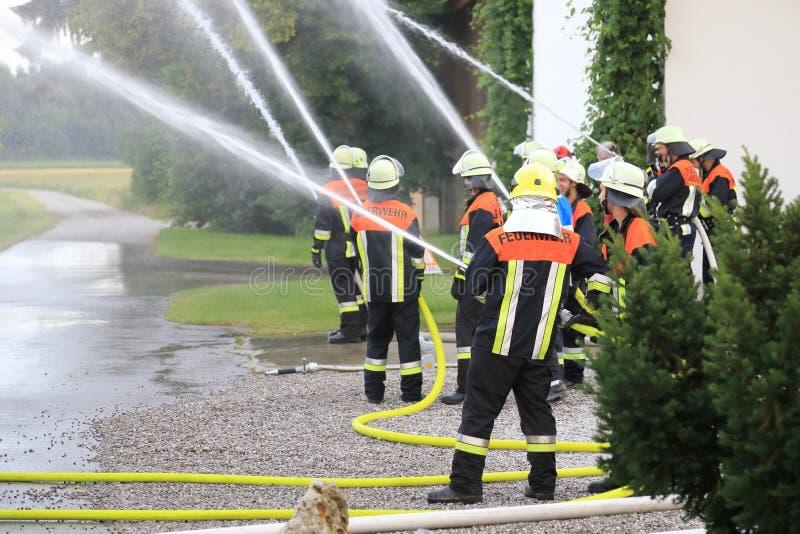 Brandbestrijdersbrandweerlieden die brand in verrichting doven royalty-vrije stock afbeeldingen