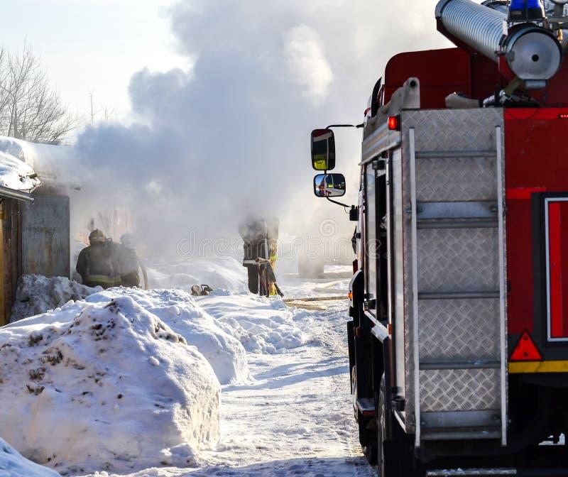 brandbestrijdings Een brandvrachtwagen en brandweerlieden op het werk Heel wat rook Uren en landschap Rusland royalty-vrije stock afbeeldingen