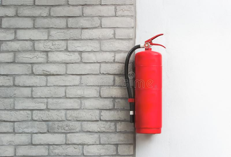 Brandblusapparaat op witte bakstenen muurachtergrond stock afbeelding