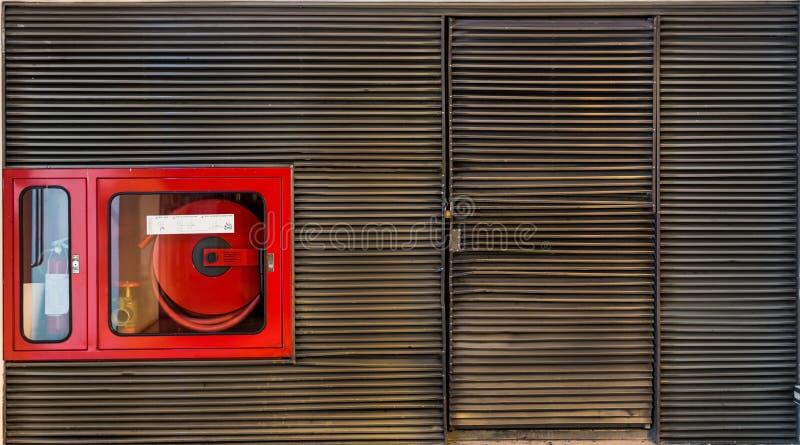 Brandblusapparaatkabinet in de de latmuur van het grungemetaal met cop royalty-vrije stock afbeelding