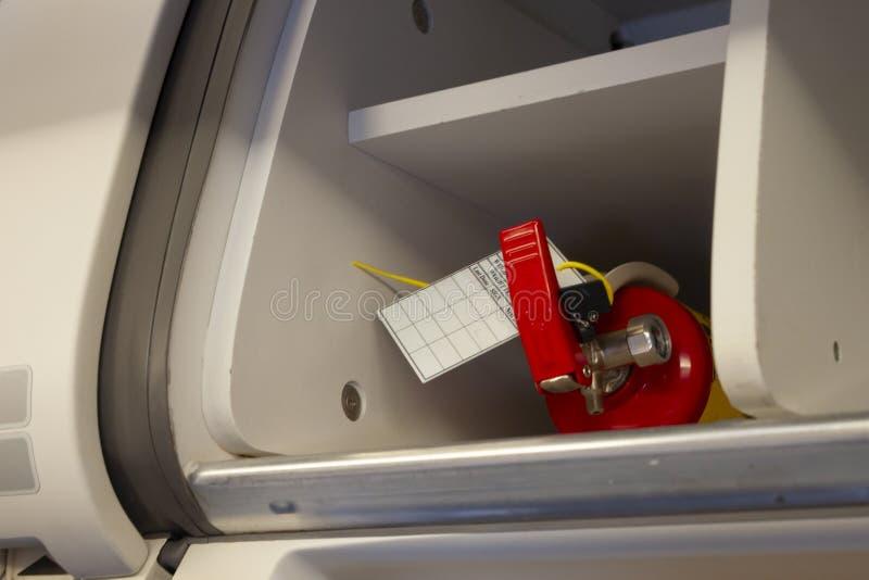 Brandblusser ligt op de bagageruimte van het vliegtuig stock afbeelding