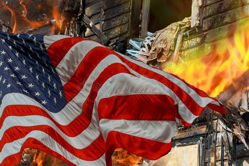 Brandbränningen i överväldigar det lilla huset och amerikanska flaggan royaltyfri foto