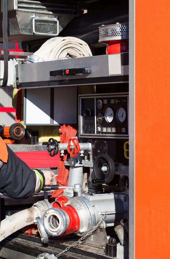 Brandbrigade in gebruik op het noodsituatievoertuig met een waterslang royalty-vrije stock afbeelding
