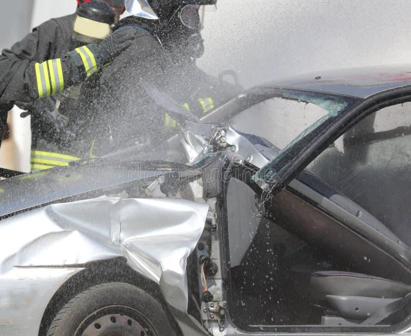 Brandbrigade tijdens brandblus van een auto na ro stock afbeeldingen