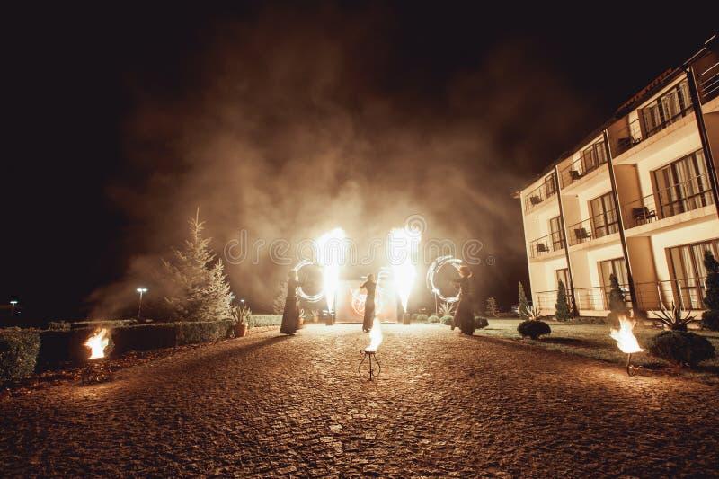 Branddansshower på natten Fantastisk brandshow som delen av bröllopceremoni arkivfoton
