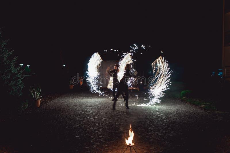 Branddansshower på natten Fantastisk brandshow som delen av bröllopceremoni royaltyfri foto