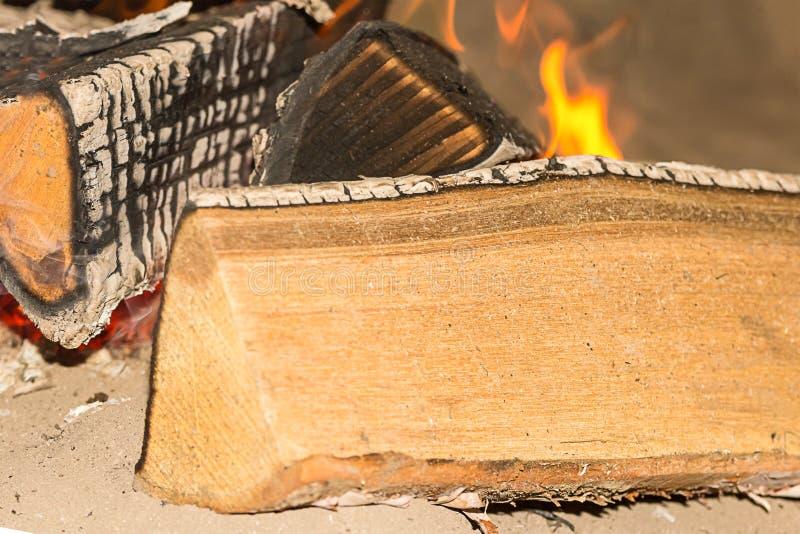 Brandde het logboek lichte beige droog op kampvuur achtergrondsteenkolen macropicknick op het ontwerp van de strandbasis royalty-vrije stock afbeelding